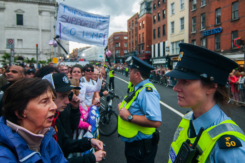 """Dublin, Ireland. 25th August, 2018. <br /> Protestors, fans and police wait the passage of Pope Francis in the afternoon along Parliament street during the first of the two-days of the visit of Pope Francis in Dublin, Ireland.<br /> Pope Francis has made a two-day visit to the Republic of Ireland by celebrating a Mass at Dublin's Phoenix Park. The Argentine Pope asked forgiveness for the """"abuses in Ireland, abuses of power, conscience and sexual abuses"""" perpetrated by Church leaders. It was the first papal visit to Ireland for 39 years. During his activities many activists, victims and survivors have made protests and a silent march Garden of Remembrance towards the last Magdalene Laundry to close in Ireland.<br />  © Simone Padovani"""