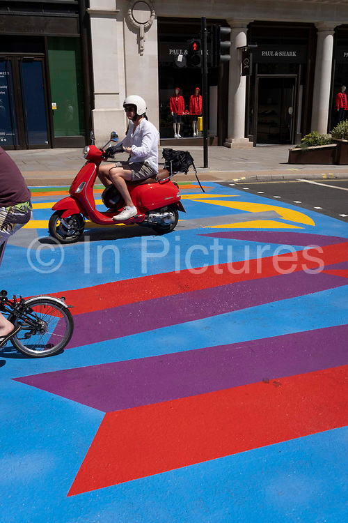 A scooter rider behind cyclist, both pass over the multi-coloured markings of a crossing at Lower Regent Street, on 16th July 2021, in London, England.