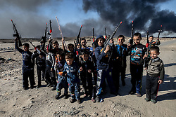 November 23, 2016 - Qayyara, Ninewa Province, IRAQ - Children play in the smoke and soot of the fires unaware of the damage that released carcinogens will do to their developing bodies for many years to come. (Credit Image: © Gabriel Romero via ZUMA Wire)