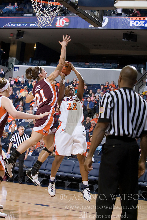Virginia's Monica Wright (22) attempts a shot against VT's Brittany Cook (21).  The Virginia Tech Hokies overcame a 14 point Virginia lead to beat the Cavaliers 60-58 on their home court at the John Paul Jones Arena in Charlottesville, VA.