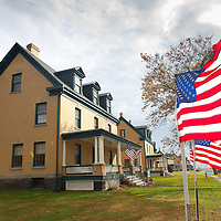 The history house along Officers Row at Sandy Hook decorated with American Flags. Sandy Hook is a large sand spit or barrier spit, the extension of a barrier peninsula along the coast of New Jersey, separated from the mainland by the estuary of the Shrewsbury River. The now-defunct Fort Hancock is located at the north end of the peninsula. It is now open to the public. The Sandy Hook Proving Ground was used by the United States Army for many years - beginning after the Civil War until 1919, when the facility was moved to Aberdeen, Maryland - and was later the site of a Nike missile defense installation. The Sandy Hook Nike station is one of a very few stations that are still intact. Almost all of the fort's gun batteries are off limits to the public due to their hazardous condition.