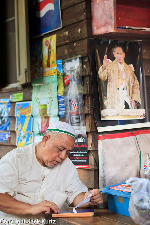 """Mar 23, 2009 -- BANGKOK, THAILAND: A Moslem storekeeper balances his books in his shop in Ban Krua. The Ban Krua neighborhood of Bangkok is the oldest Muslim community in Bangkok. Ban Krua was originally settled by Cham Muslims from Cambodia and Vietnam who fought on the side of the Thai King Rama I. They were given a royal grant of land east of what was then the Thai capitol at the end of the 18th century in return for their military service. The Cham Muslims were originally weavers and what is known as """"Thai Silk"""" was developed by the people in Ban Krua. Several families in the neighborhood still weave in their homes.     Photo by Jack Kurtz"""