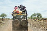 Car loaded with many local people on the roof, driving in savana, near Lake Eyasi, Tanzania
