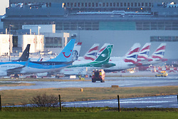 © Licensed to London News Pictures. 20/12/2018. London, UK. A fire engine passes parked passenger aircraft at Gatwick airport. Flights have been cancelled and thousands of passengers have been delayed after the airport closed due to two drones being spotted nearby. Photo credit: Peter Macdiarmid/LNP