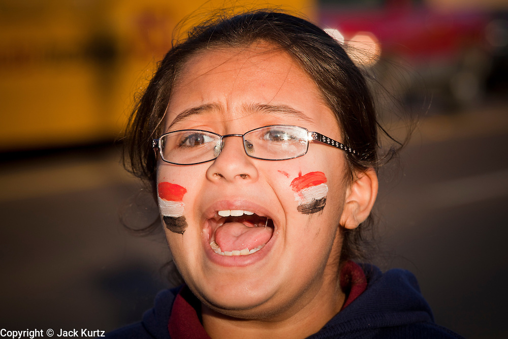 31 JANUARY 2011 - TEMPE, AZ: A girl with Egyptian flags painted on her cheeks at a demonstration supporting democracy in Egypt. About 200 people marched through central Tempe, AZ, near the Arizona State University campus Monday afternoon. The rally was organized by the Arab American Association of Arizona in solidarity with the ongoing pro-democracy rallies and demonstrations in Egypt and other Arab countries.    Photo by Jack Kurtz