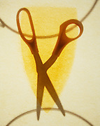 pair of open scissors seen through a hot iron scorched background.