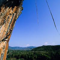 Tamotsu Sugino climbs the orange arete Mind the Bees, 5.13a,  over the Nam Ou River, Ban Pak Ou, Luang Phrabang, Laos