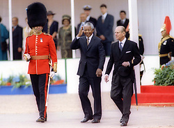 South African President Nelson Mandela, accompanied by the Duke of Edinburgh (R), prepares to review an honour guard on Horse Guards Parade, on the first day of his state visit to Britain.