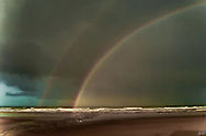 """This double rainbow appeared on a very stormy day along the west coast. The few folks on the beach were """"braving"""" it. The dark sky with a touch of blue was compelling."""