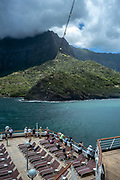 Tourists on board a cruise ship photograph the island of  Hiva Oa, Marquesas Islands, French Polynesia.<br /> Hiva Oa is the second largest island in the Marquesas Islands, an overseas territory of France in the Pacific Ocean.