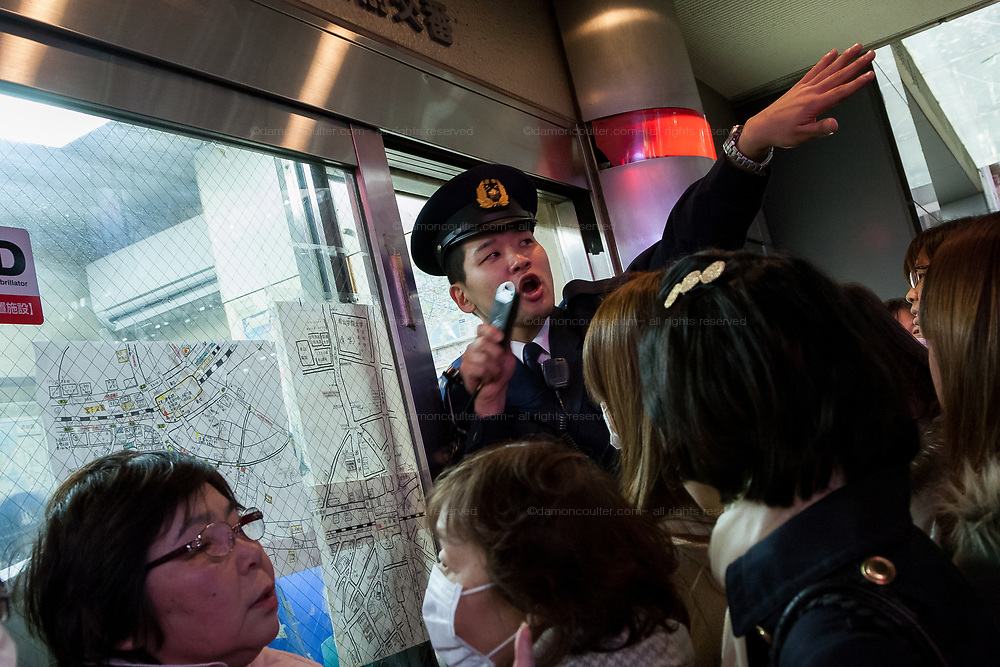 Policemen at the police box next to Shibuya Station help people with after a magnitude 9 earthquake hit the Tohoku region of Japan causing tremors in Tokyo that stopped the train and cellphone networks. Many people were stranded in the centre of Tokyo over night. Tokyo, Japan Friday March 11th 2011