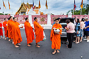 """21 JULY 2013 - BANGKOK, THAILAND:  People present monks with alms and make merit at Wat Benchamabophit on the first day of Vassa, the three-month annual retreat observed by Theravada monks and nuns. On the first day of Vassa (or Buddhist Lent) many Buddhists visit their temples to """"make merit."""" During Vassa, monks and nuns remain inside monasteries and temple grounds, devoting their time to intensive meditation and study. Laypeople support the monastic sangha by bringing food, candles and other offerings to temples. Laypeople also often observe Vassa by giving up something, such as smoking or eating meat. For this reason, westerners sometimes call Vassa the """"Buddhist Lent.""""       PHOTO BY JACK KURTZ"""