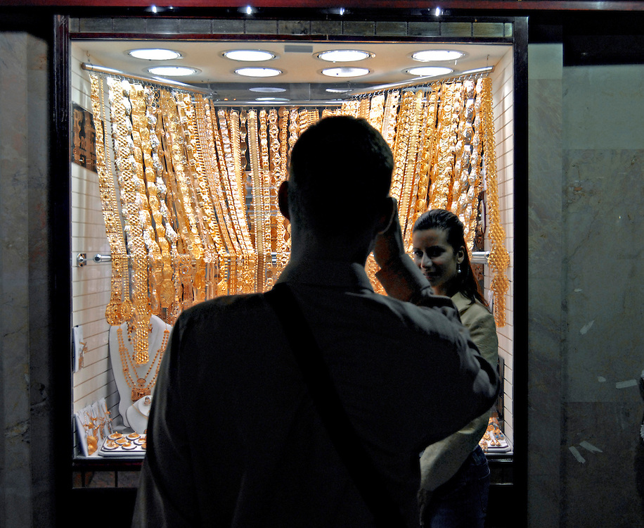 Paar vor Geschäft mit Goldauslage      man takes a picture of a woman in front of a shop with golden jjewellery    