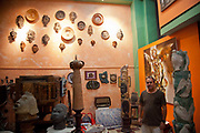 Local Cuban artist in his studio posing for a portrait with his sculptures.