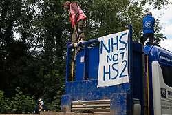 A Thames Valley Police officer speaks to an anti-HS2 activist secured with a large rope around his neck who is blocking a HGV used for works connected to the HS2 high-speed rail link on 28 September 2020 in Denham, United Kingdom. Environmental activists continue to try to prevent or delay works on the controversial £106bn project for which the construction phase was announced on 4th September from a series of protection camps based along the route of the line between London and Birmingham.