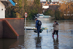 © Licensed to London News Pictures. 12/01/2014. Reading, Berkshire, UK. Members of Reading Rowing Club arriving for Sunday morning training along the Thames Path in Reading, Berkshire. The River Thames has broken its banks causing extensive flooding. Photo credit : Rob Arnold/LNP