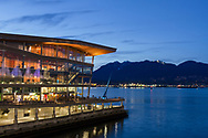The Vancouver Convention Center in the early evening. Photographed from the area in between the Vancouver Convention Center and Canada Place in Vancouver, British Columbia, Canada.  The North Shore Mountains (and North Vancouver) are in the background across Burrard Inlet.