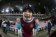 a Young West Ham United fans cheers on his team during pre match warm up. The Emirates FA cup, 4th round replay match, West Ham Utd v Liverpool at the Boleyn Ground, Upton Park  in London on Tuesday 9th February 2016.<br /> pic by John Patrick Fletcher, Andrew Orchard sports photography.