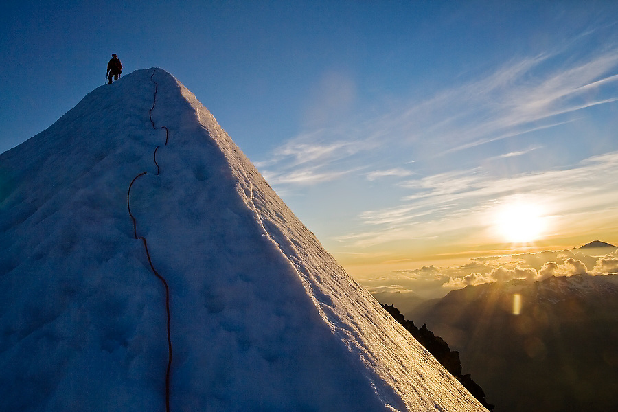A climber stands atop the thin snow ridge at the summit of Eldorado Peak in the heart of the North Cascades National Park, Washington, as the sun sets in the distance.