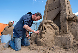 "© Licensed to London News Pictures. 12/05/2019. Weston-super-Mare, North Somerset, UK. The Weston-super-Mare Sand Sculpture Festival at Weston's beach. A Brexit related sand sculpture ""Off With My Head"" is worked on by Dutch artist JOHANNES HOGEBRINK (pictured). The sculpture depicts a large globe and in the centre of it is Theresa May putting her head under a falling guillotine, with Vladimir Putin and Donald Trump watching the spectacle of Brexit. The piece stands 4m tall and 6m wide and will take a total of 8 days to complete. The Weston Sand Sculpture Festival promises a new theme each year and this year the broad ""What If…?"" topic has allowed artists to create conceptual pieces of art portraying some important and alarming messages from Climate Change to Feminism. Photo credit: Simon Chapman/LNP"