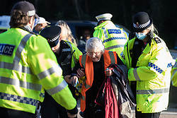 Ockham, UK. 21st September, 2021. Surrey Police officers remove Insulate Britain climate activist Reverend Sue Parfitt from the clockwise carriageway of the M25 between Junctions 9 and 10 where she had been protesting as part of a campaign intended to push the UK government to make significant legislative change to start lowering emissions. Both carriageways were briefly blocked before being cleared by Surrey Police. The activists are demanding that the government immediately promises both to fully fund and ensure the insulation of all social housing in Britain by 2025 and to produce within four months a legally binding national plan to fully fund and ensure the full low-energy and low-carbon whole-house retrofit, with no externalised costs, of all homes in Britain by 2030.