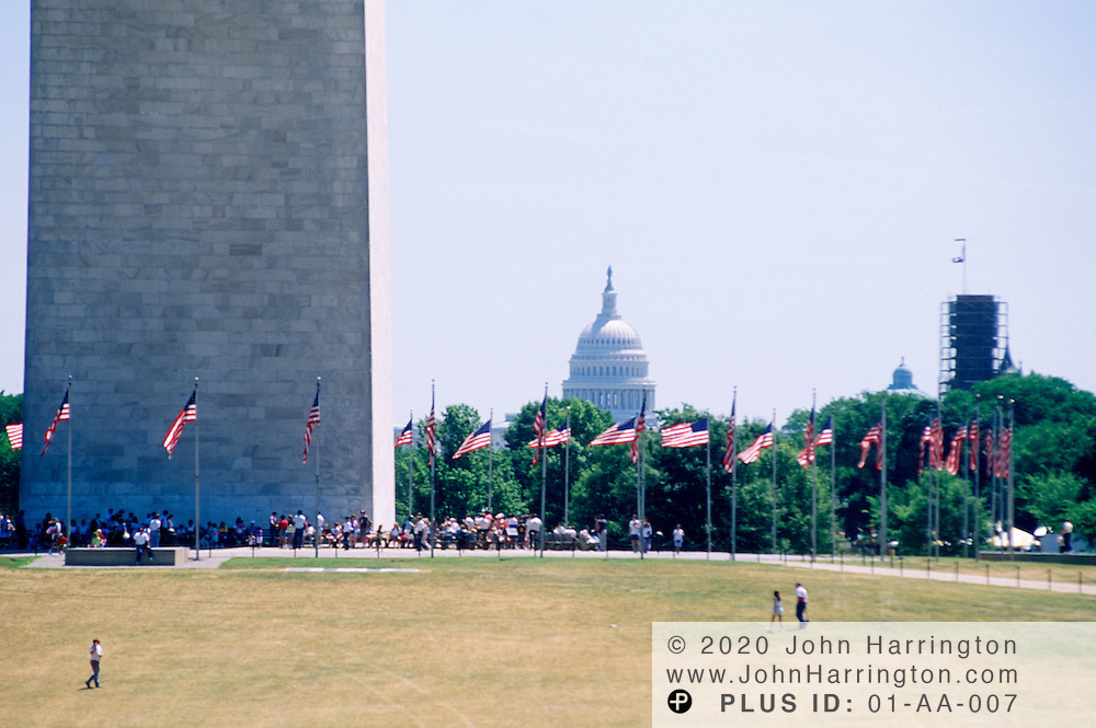 FLAGS AROUND WASHINGTON MONUMENT WITH US CAPITOL IN BACKGROUND.