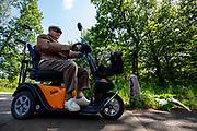 Een man in een scootmobiel rijdt over een fietspad in de bossen tussen Soest en Den Dolder.<br /> <br /> A man on a scooter rides at the cycle path between Soest and Den Dolder