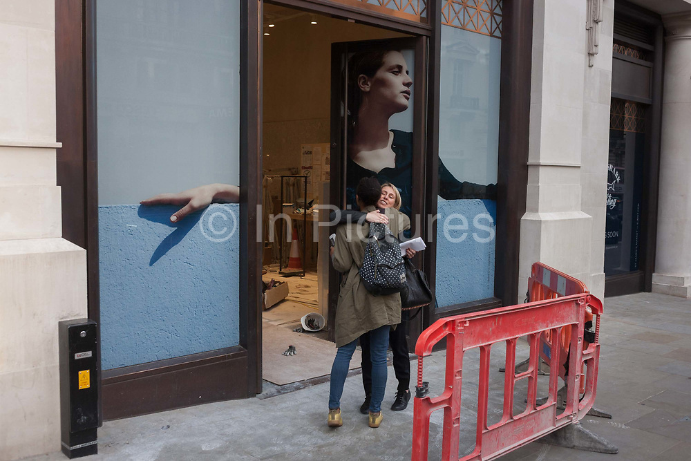 Two women hug while greeting each other beneath a retail poster for a new Jigsaw clothing shop, on 29th September 2016, in central London. Warmly hugging in a spontaneous moment of friendship, the women hold on tight before entering the new store premises.