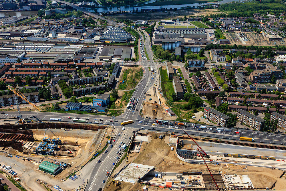 Nederland, Limburg, Maastricht, 27-05-2013; bouwwerkzaamheden voor de A2 traverse, De Groene Loper. <br /> Kruispunt Geusselt met  tunnelbouwkuip, naar links het verkeer richting centrum. Maas boven in beeld.<br /> De snelweg A2 gaat ondergronds, er wordt een gestapelde tunnel gebouwd (2 wegen boven elkaar). Het plan moet voor een betere bereikbaarheid en leefbaarheid van Maastricht zorgen en ook voor een betere doorstroming op de A2.<br /> Construction works for motorway A2 crossing Maastricht, the so-called Green Carpet.<br /> The A2 motorway goes underground, a stacked tunnel is  built with two roads above each other). The plan should provide better accessibility and traffic flow.<br /> luchtfoto (toeslag op standard tarieven);<br /> aerial photo (additional fee required);<br /> copyright foto/photo Siebe Swart.