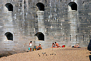 Holidaymakers on the beach at Portsmouth Harbour dwarfed by the huge Napoleonic defensive  wall. Portsmouth, UK