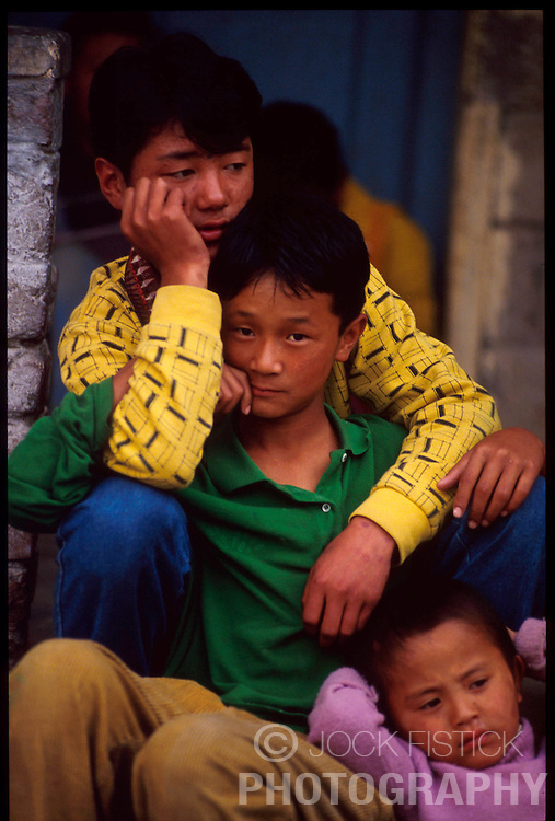 DHARAMSALA, INDIA -OCTOBER 1992 - Tibetan refugee children cling to each other at a school for Tibetan Refugees in Dharamsala, India. The Tibetan children's Village runs a chain of fifteen schools, with over ten thousand students, in different parts of India. The main village, known as the Upper TCV, is based on a hill two kilometres from McLeod Ganj. It educates and looks after the upbringing of about three thousand student, most of whom are orphans and new refugees from Tibet. Upper TCV consists of thirty eight homes, four hostels and a baby room to care for months-old infants through to boys and girls of sixteen. It has modern school buildings ranging from nursery to high school, sports grounds, staff quarters, a dispensary, a handicraft centre, etc. These are spread over an area of about forty three acres. (Photo © Jock Fistick)
