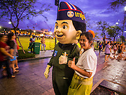 """24 JULY 2014 - BANGKOK, THAILAND: A woman poses for a selfie with a Thai military mascot character at the happiness party in Bangkok. The Thai Junta is organizing a series of public events throughout Thailand meant to bolster public opinion. The events are called """"restoring happiness to the people"""" parties. They feature historic pageants, music, food, health checks and free haircuts. The party in Bangkok is on Sanam Luang, the Royal Parade Ground, which is near the Grand Palace and the Ministry of Defense.    PHOTO BY JACK KURTZ"""