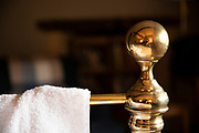 Generic image of the concept of a hotel stay - white cotton towel on old brass bedhead with traditional knob in a quaint hotel bedroom in The Cotswolds, UK
