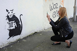 "© Licensed to London News Pictures. 31/10/2015. Folkestone, UK. SOFIE VIAENE taking a picture of artwork by the artist BANKSY, next to the location of a BANKSY piece that was removed. The Artwork pokes fun at the removal of the last piece which was called ""Art Buff"", which was of an old lady, and says ""IF FOUND PLEASE CONTACT ALASTAIR. Alastair Upton is the Chief Executive of the Creative Foundation who as called for the picture to be returned to the town. Photo credit:Grant Falvey/LNP"