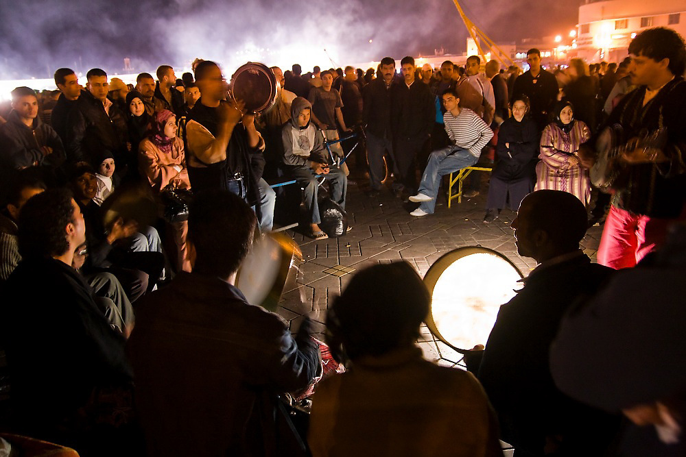 Traditional musicians and storytellers perform into the night among a large crowd of locals and Moroccan tourists in the Djemaa El-Fna Square in the heart of the Marrakech medina, Morocco.