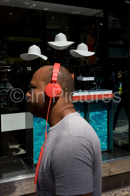 Man listening to mp3 music walks past a sunglasses shop featuring three hats suspended from the store window ceiling. The male consumer passes the dark window selling summer eyewear in London's Long Acre, a street near the capital's Covent Garden, Westminster. With red headphones covering his ears - and with a red coil of wiring down his chest, we see the three white hats that symbolise a London summer, hanging in clear space above the woman's head.