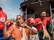 25 OCTOBER 2015 - SHWEPYITHAR, MYANMAR: A National League for Democracy (NLD) supporter dance during motorcade in Shwepyithar, Myanmar. Political parties are in fill campaign mode in Myanmar (Burma). National elections are scheduled for Sunday Nov. 8. The two principal parties are the National League for Democracy (NLD), the party of democracy icon and Nobel Peace Prize winner Aung San Suu Kyi, and the ruling Union Solidarity and Development Party (USDP), led by incumbent President Thein Sein. There are more than 30 parties campaigning for national and local offices.     PHOTO BY JACK KURTZ