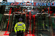 """A police officer talks to the activists that are sat on the doors of the bank Standard Chartered, which has been covered in red paint during an Extinction Rebellion climate change protest in the city of London on Friday, 27 Aug 2021. This is their fifth day of an ongoing two-week disruption protest campaign """"The Impossible Rebellion"""". (VX Photo/ Vudi Xhymshiti)"""