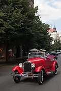 Man driving an antique vintage 1930's car in excellent condition; Prague, Czech Republic.