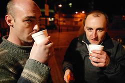 Men enjoying hot drinks from a mobile soup kitchen in Nottingham,