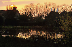 Reflections on the horsepond at Great Dixter at sunset