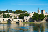 View of the Pont Saint-Bénézet, also called the Pont d'Avignon, on a beautiful summer day on the Rhone River in Avignon, France. The four surviving arches are believed to have been built in around 1345 by Pope Clement VI during the Avignon Papacy. The golden statue is part of the Avignon Cathedral (Notre Dame des Doms), seat of the Archbishop.