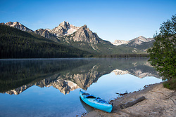 A kayak awaits its paddler to become one with the reflection beyond.  McGown Peak reflecting in the waters of Stanley Lake in the Sawtooth National Recreation Area of Central Idaho