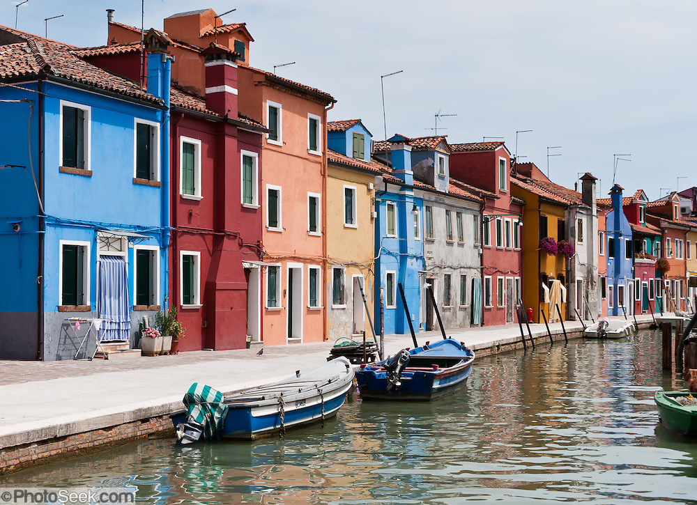 """Blue boats, canal, and houses painted blue, red, orange, yellow. Burano, known for knitted lacework, fishing, and colorfully painted houses, is a small archipelago of four islands linked by bridges in the Venetian Lagoon, northern Italy, Europe. Burano's traditional house colors are strictly regulated by government. The Romans may have been first to settle Burano. Romantic Venice (Venezia), """"City of Canals,"""" stretches across 117 small islands in the marshy Venetian Lagoon along the Adriatic Sea in northeast Italy, between the mouths of the Po (south) and Piave (north) Rivers. Venice and the Venetian Lagoon are honored on UNESCO's World Heritage List."""