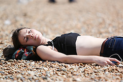 © Licensed to London News Pictures. 16/06/2015. Brighton, UK. People take advantage of the sunny weather to relax in the sun on Brighton Beach, today June 16th 2015. Photo credit : Hugo Michiels/LNP