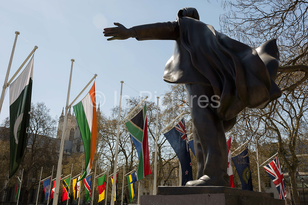 With the statue of Liberal statesman David Lloyd-George in the foreground, the flags of all Commonwealth Nations hang in Parliament Square on the occasion of the bi-annual Commonwealth Heads of Government Meeting CHOGM,  on 19th April 2018, in London, England.