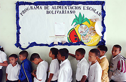 """Students at the Florencio Jimenez school wait in line for lunch.  The school is one of the new """"Bolivarian"""" Schools which are part of President Chavez's Education Reform.  The new Bolivarian Schools keep students for an entire day, as opposed to a half day, feed the students lunch and offer programs like drama, art and music.  The sign above the students reads """"Bolivarian School Food Program"""".  While President Chavez touts his programs that benefit the poor, many point to a rising poverty rate and shrinking economy and claim the programs fail to substantially help."""