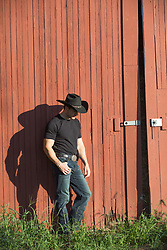 hot young cowboy against a rustic barn
