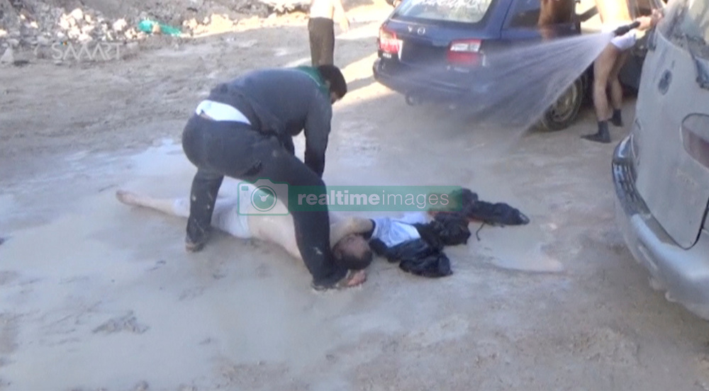 April 4, 2017 - Khan Sheikhoun, Syria - Medics spray down a victim lying on the ground, hurt  by what rescue workers described as a suspected gas attack (most likely sarin never gas), in rebel-held Idlib, Syria. Idlib is a city in northwestern Syria, capital of the Idlib Governorate, near Turkey and 59 kilometers south west of Aleppo. It has an elevation of nearly 500 meters above sea level, population around 165,000. The inhabitants are overwhelmingly Sunni Muslims, although there is a significant Christian minority. (Credit Image: © Edlib Media Center via ZUMA Wire)