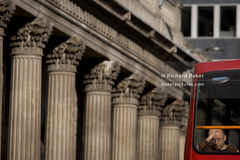 Columns of the Bank of England and tired top-deck bus passenger in the City of London.